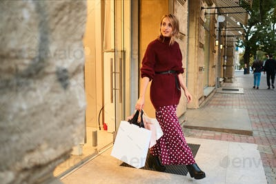 Attractive stylish blond girl in knitted sweater with shopping bags leaving store after shopping