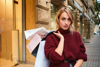 Attractive blond girl in knitted sweater with shopping bags confidently looking in camera on street