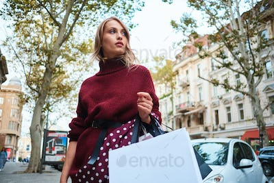 Gorgeous stylish blond girl with shopping bags thoughtfully looking away on city street