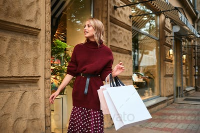 Stylish blond girl in knitted sweater with shopping bags dreamily walking through city street