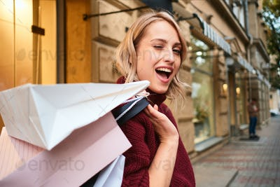 Portrait of cheerful blond girl with shopping bags happily winking out on city street