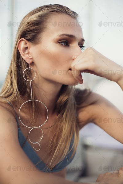 Young beautiful woman with blond hair wearing big modern earring thoughtfully looking aside outdoor