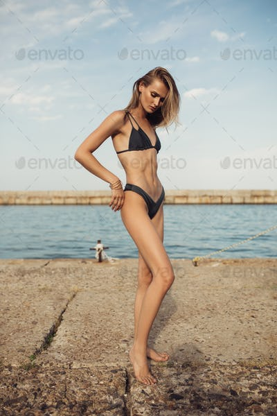 Young attractive woman with blond hair in black swimsuit wearing jewelry on beach