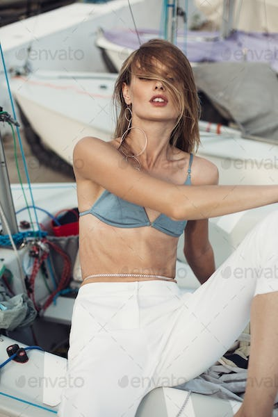 Model in swimsuit and white trousers wearing jewelry sensually leaning on boat