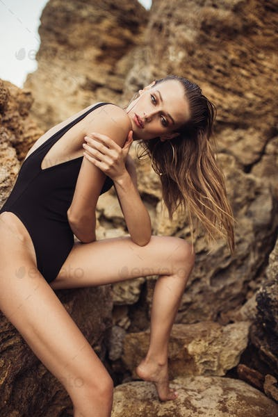 Gorgeous girl in black swimsuit wearing gold earrings sitting on rock sensually posing on seaside