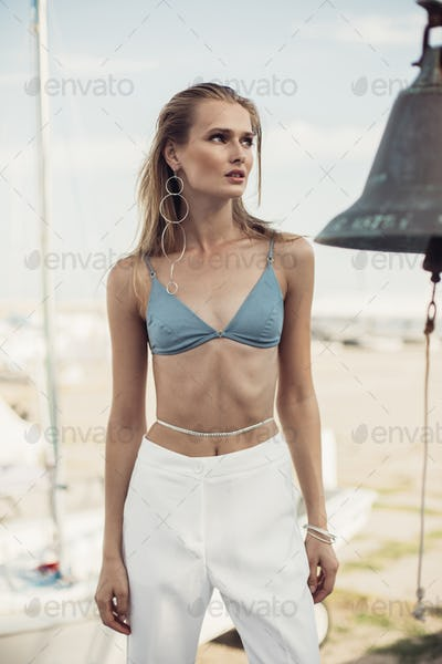 Sensual girl in swimsuit top and white trousers wearing modern earring and body jewelry at seaside