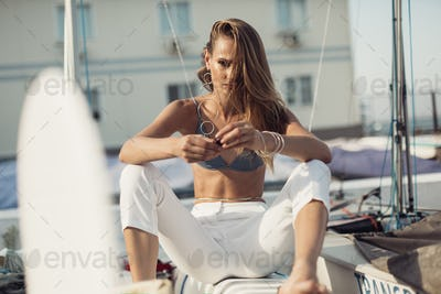 Young woman in swimsuit trousers and jewelry sitting on boat at seaside