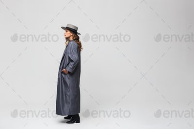 Young woman in hat and cloak holding hand in pocket looking aside over gray background