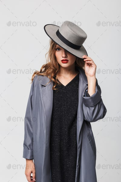 Young attractive woman with wavy hair in cloak covering eye with hat thoughtfully looking in camera