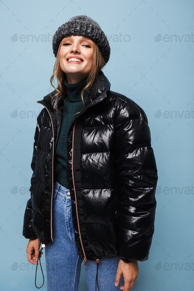 Young pretty smiling woman in knitted hat and black down jacket joyfully looking in camera