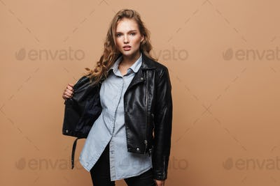 Young pretty woman with wavy hair in black leather jacket and shirt thoughtfully looking in camera