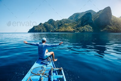 Back view of the man on boat with spreading hands arriving to exotic tropical island lit by sun