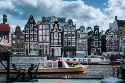 Amsterdam canal Singel with typical dutch houses and houseboats with beautiful cloudscape in