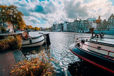 Amsterdam canal Singel with typical dutch houses and houseboats during sunny autumn day. Golden