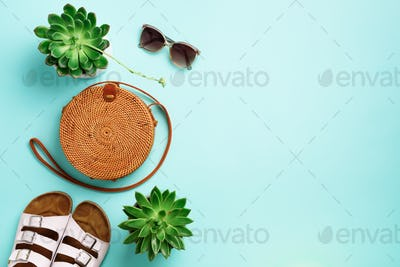 Stylish rattan bag, birkenstocks, succulent, sunglasses on blue background. Banner. Top view with