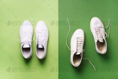 Old dirty sneakers vs new white sneakers on green background. Trendy footwear. Top view. Concept of