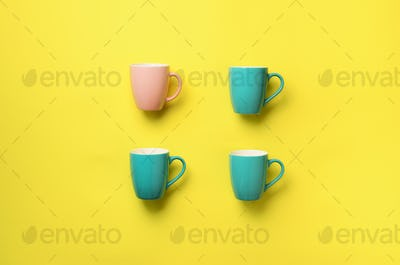 Pattern from blue cups over yellow background. Birthday party celebration, baby shower concept