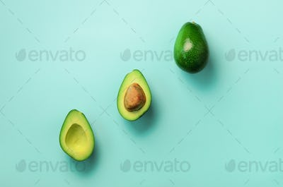 Organic avocado with seed, avocado halves and whole fruits on blue background. Top view. Pop art