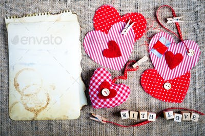 Red polka dot textile hearts on burlap. Free space for your text
