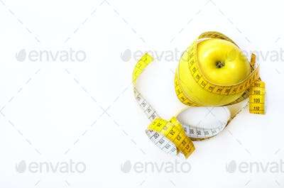 Measuring tape wrapped around fresh tasty yellow apple isolated on white background. Diet, weight
