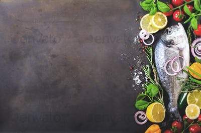 Dorada, fresh fish with vegetable, lemon, herbs, onion, paprika, cherry tomatoes, onion, salton dark