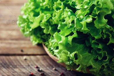 Fresh organic lettuce salad on wooden background with pepper. Healthy food, raw and vegetarian