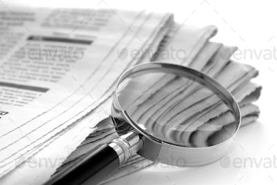 newspaper and a magnifying glass
