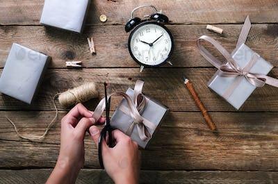 Beautiful woman hands holding gift box on wooden background. Black alarm clock, pen, scissors