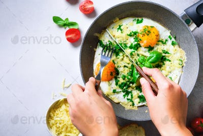 Girl hands above frying pan with three cooked eggs, herbs, cheese, tomatoes. Woman is making