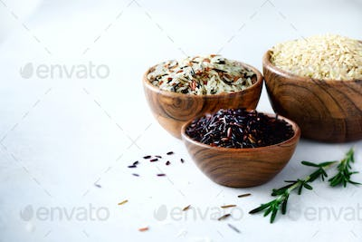 Jasmine white rice, brown, black and red rice. Mixed assortment of grains in wooden bowls on grey