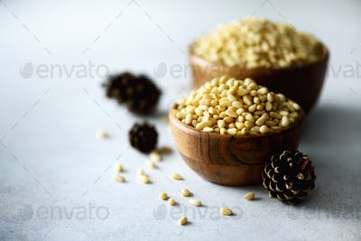 Shelled organic pine nuts in wooden bowl. Nuts background. Top view, copy space