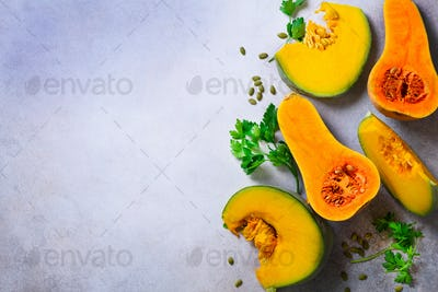 Cut ripe orange pumpkin with seeds and herbs on light grey background. Vegetarian and raw organic