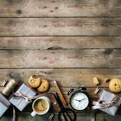 Gift boxes, black alarm clock, pen, scissors on wooden background. Preparing for birthday, christmas