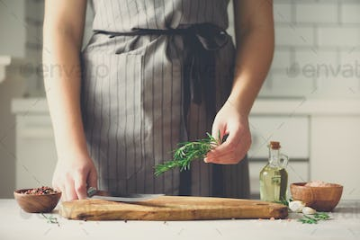 Woman hands cutting fresh green rosemary on wood chopping board in white kitchen, interior. Copy
