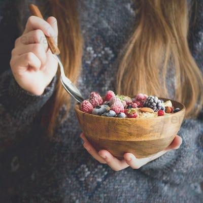Girl hands holding oatmeal porridge with frozen berries, almonds in wooden bowl. Healthy breakfast