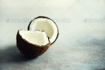 Cracked two halves of fresh organic coconut on grey background. Copy space
