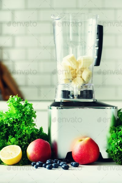 Woman blending lettuce leaves, spinach, aplles, berries, bananas. Homemade healthy green smoothie