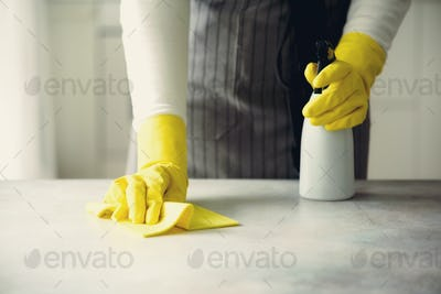 Woman in yellow rubber protective gloves wiping dust and dirty. Cleaning concept, banner, copy space