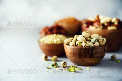 Pistachios nuts in wooden bowl. Food mix background, top view, copy space, banner. Assortment of