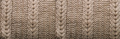 Knitted texture. Pattern fabric made of wool. Background, copy space. Banner
