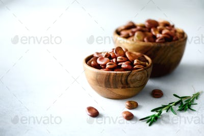 Organic dried broad beans in wooden bowls and rosemary on gray concrete background. Fava Vicia beans