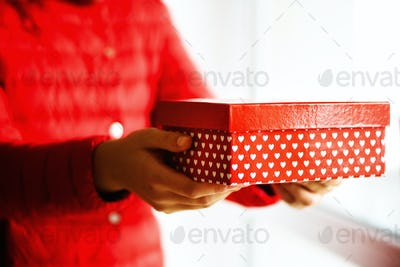 Female hands holding red gift box with white hearts, copy space. Christmas, hew year, birthday