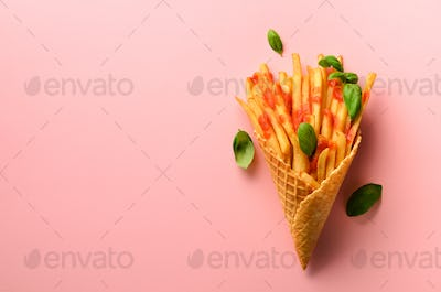 Fried potatoes in waffle cones on pink background. Hot salty french fries with sauce, basil leaves