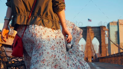 Young woman with a retro camera on the Brooklyn Bridge