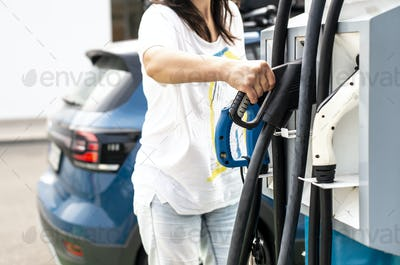 Woman charge Electric car on gas station. Blue car and electric