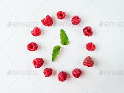 Clock made of raspberries, white backround