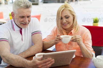 Mature couple using digital tablet in outdoors of cafe