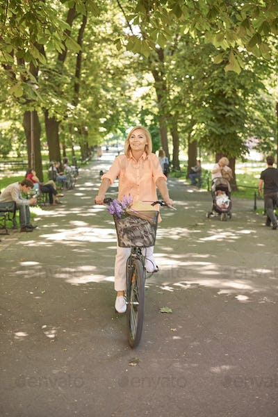 Attractive adult woman riding a bike