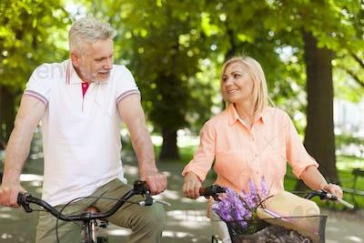 Loving mature couple riding on the bike at park