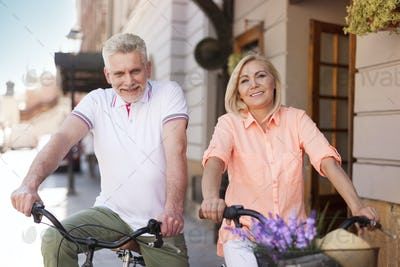 Mature couple riding on bike in city